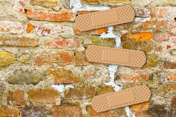 renovation of cracked brick wall - concept image with copy space - stability stock photos and pictures
