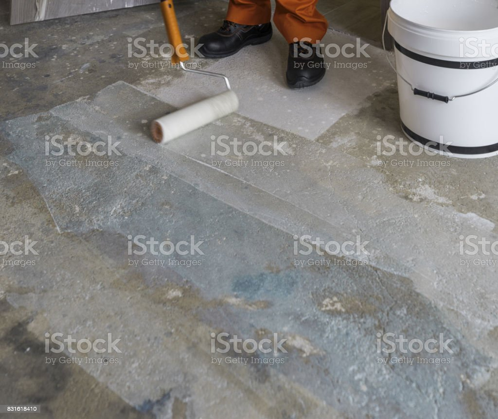 Renovation of house. Worker puts primer with roller on concrete floor stock photo