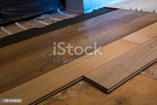 922081754istockphoto Renovation works. Close-up of installation of parquet and ceramic tile floor and heating cables for warm floor. 1081649062