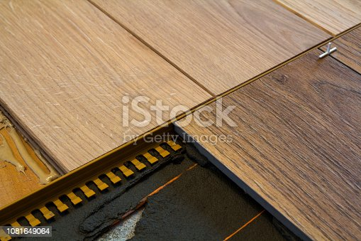 922081754istockphoto Renovation works. Close-up of installation of parquet and ceramic tile floor and heating cables for warm floor. 1081649064