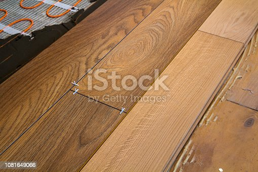922081754istockphoto Renovation works. Close-up of installation of parquet and ceramic tile floor and heating cables for warm floor. 1081649066