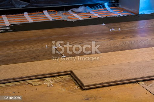 922081754istockphoto Renovation works. Close-up of installation of parquet and ceramic tile floor and heating cables for warm floor. 1081649070