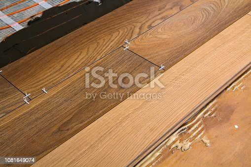 922081754istockphoto Renovation works. Close-up of installation of parquet and ceramic tile floor and heating cables for warm floor. 1081649074