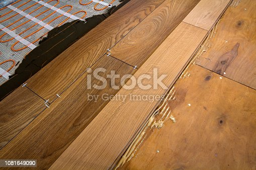 922081754istockphoto Renovation works. Close-up of installation of parquet and ceramic tile floor and heating cables for warm floor. 1081649090