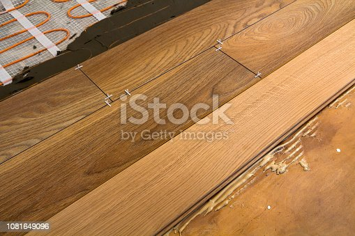922081754istockphoto Renovation works. Close-up of installation of parquet and ceramic tile floor and heating cables for warm floor. 1081649096