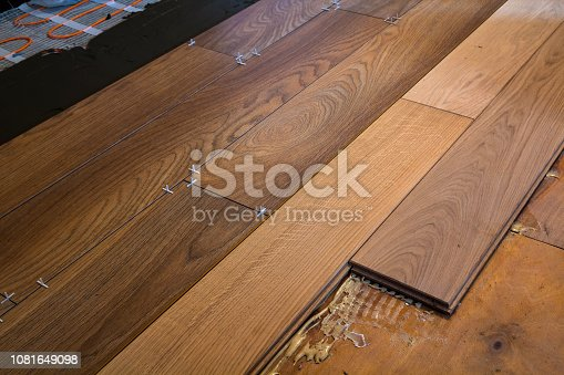 922081754istockphoto Renovation works. Close-up of installation of parquet and ceramic tile floor and heating cables for warm floor. 1081649098