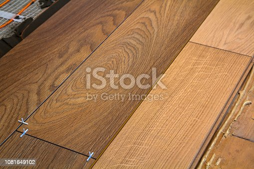 922081754istockphoto Renovation works. Close-up of installation of parquet and ceramic tile floor and heating cables for warm floor. 1081649102