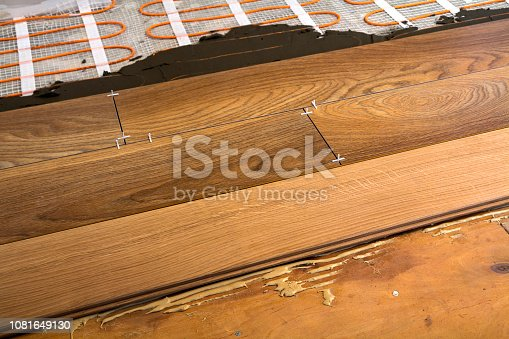 922081754istockphoto Renovation works. Close-up of installation of parquet and ceramic tile floor and heating cables for warm floor. 1081649130