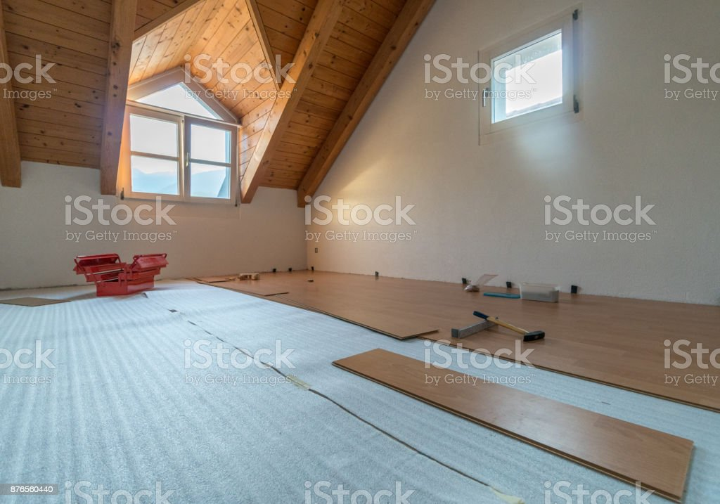 empty room with red toolbox and wooden flooring during renovations in...