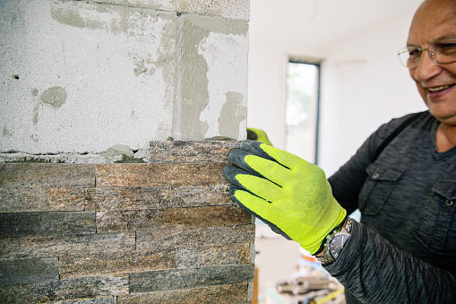 Man putting natural stone on the fireplace