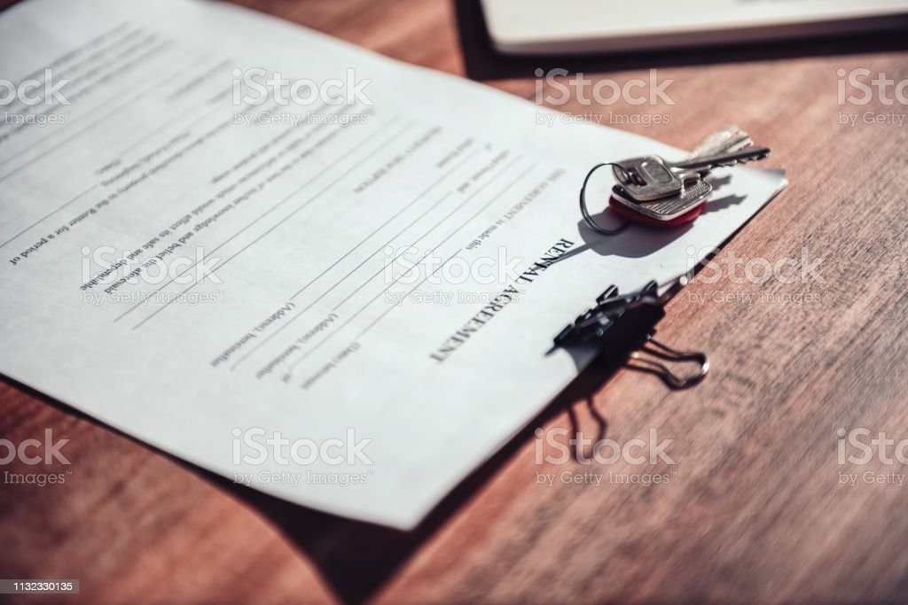 Blank rental agreement contract and keys on the desk