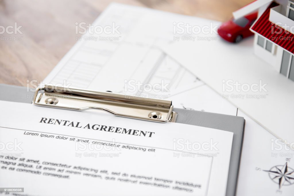 Rental agreement contract paper with blueprints and house model on...