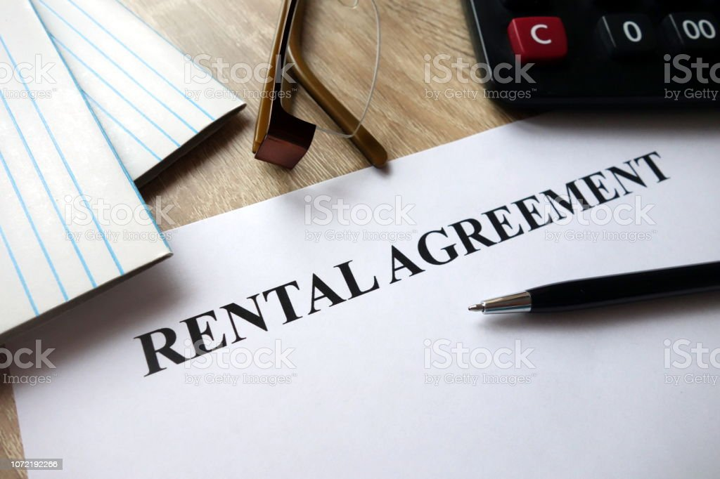 Rental agreement form with pen, calculator and glasses on desk stock photo