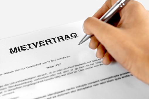 626187670 istock photo Rental agreement form with signing hand - German word