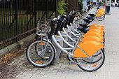 Rental bicycles standing in row on street. Rental bicycles on parking in european city.