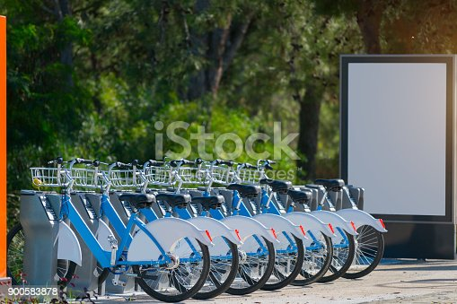 Rental bicycles standing in row on street .With white emty blank board at back