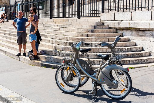 Paris, France - Jul 06, 2016: Rental bicycles with tourists front of the Sacre-Coeur Basilica in Paris, France.