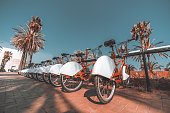 A long row of rental red parked bicycles on Barcelona street surrounded by palm trees; wide-angle view of the bikes plugged into their parking place and stretching into the distance on a sunny day