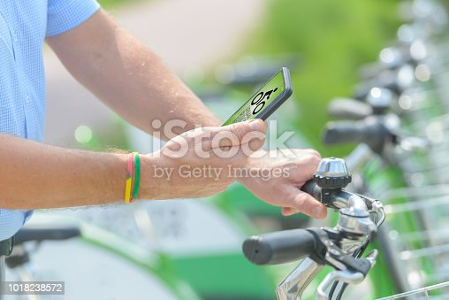 istock Renting bicycle from urban bicycle sharing station 1018238572