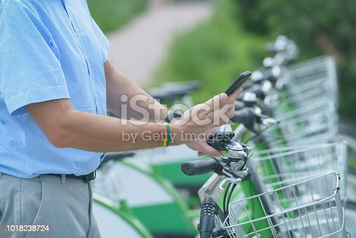 istock Renting bicycle from urban bicycle sharing station 1018238724
