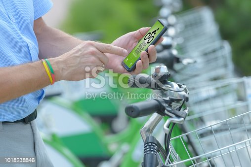 istock Renting bicycle from urban bicycle sharing station 1018238846