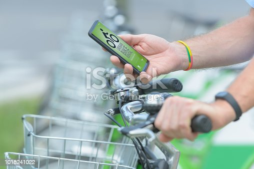 istock Renting bicycle from urban bicycle sharing station 1018241022