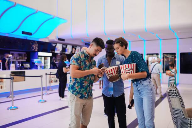 Reopening Cinema After Coronavirus - Three Friends Talking In Cinema Lobby stock photo