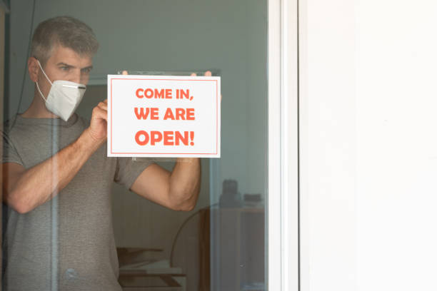 """Reopening for business adapt to new normal due the Coronavirus COVID-19 pandemic. A business owner wearing medical mask placing open sign """"COME IN, WE ARE OPEN"""" on front door stock photo"""