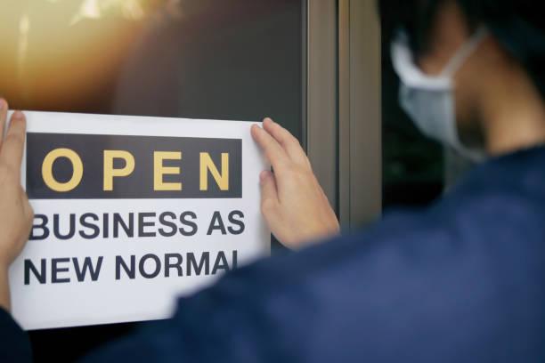 """ponowne otwarcie dla biznesu dostosować się do nowych normalnych w powieści coronavirus covid-19 pandemii. widok z tyłu właściciela firmy na sobie maskę medyczną umieszczenie otwartego znaku """"open business as new normal"""" na drzwiach wejściowych. - plecy zdjęcia i obrazy z banku zdjęć"""