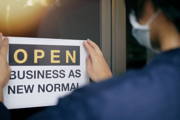 "reopening for business adapt to new normal in the novel coronavirus covid-19 pandemic. rear view of business owner wearing medical mask placing open sign ""open business as new normal"" on front door. - business stock pictures, royalty-free photos & images"