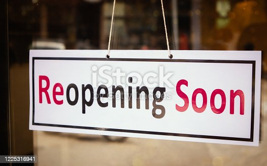 istock Reopening Soon Signage board in front of Businesses or Restaurant door after covid-19 or coronavirus outbreak - Concept of back to business after pandemic 1225316941