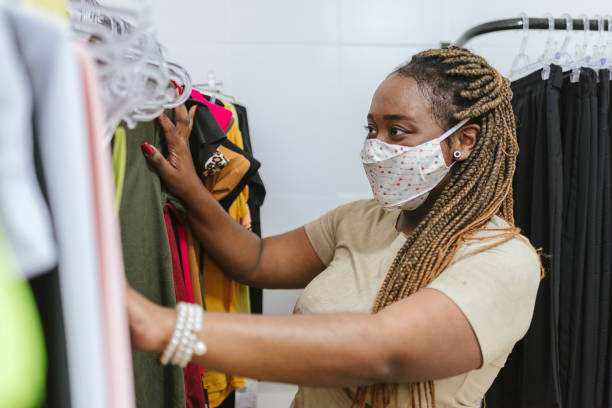 reopening: woman customer wearing mask in clothing store - afro latino mask imagens e fotografias de stock