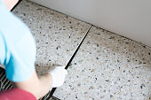 Repair and decoration of apartments and houses. Professionals lay porcelain tiles on the floor in the bathroom