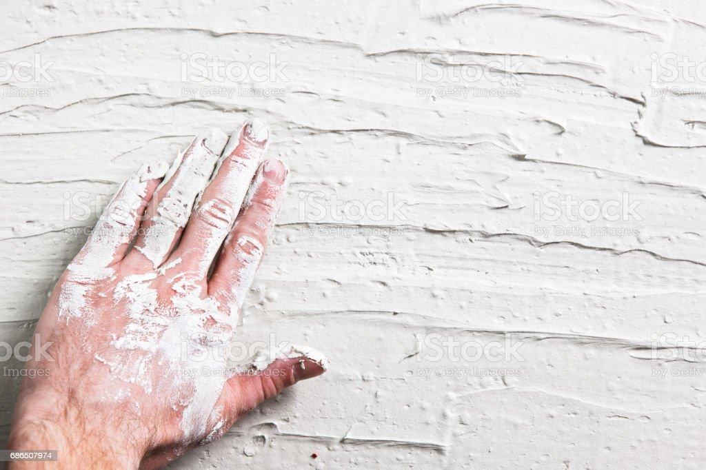 Reparatie achtergrond. Gips muur met werknemer hand. royalty free stockfoto