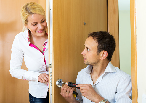 Home Repairman helps a woman secure the home. Focus on the man