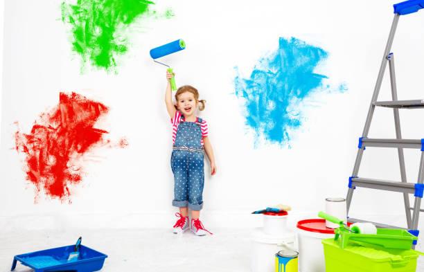 in der wohnung zu reparieren. glückliches kind mädchen farben wand - lustige babybilder stock-fotos und bilder