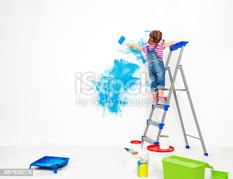 istock Repair in apartment. Happy child girl paints wall 657926276
