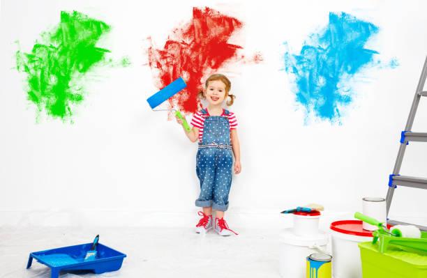 repair in apartment. happy child girl paints wall - lustige babybilder stock-fotos und bilder