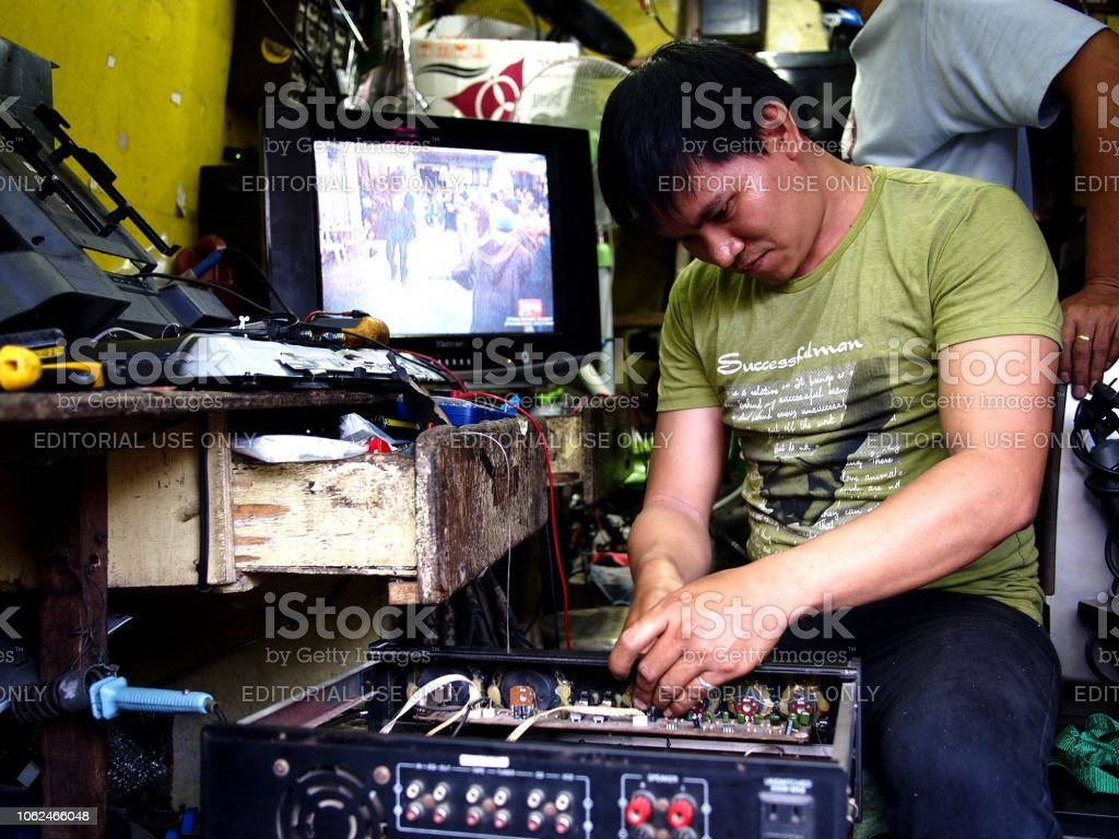 A repair man fixes an electronic household item at his repair shop. stock photo
