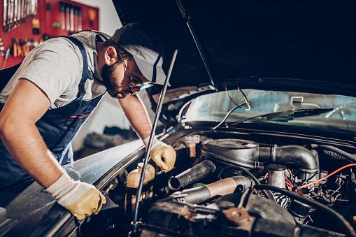 Repair man working in garage on repair of old timer