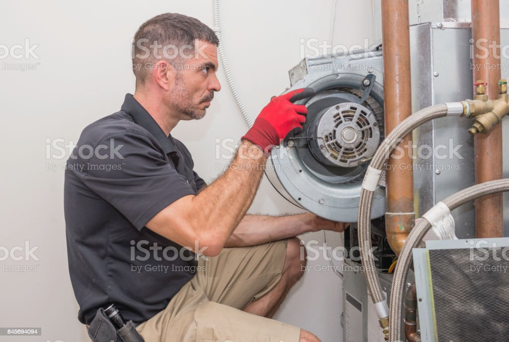 HVAC repair man working on a heat pump royalty-free stock photo