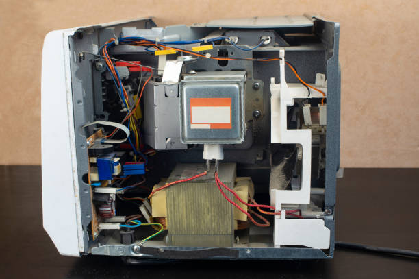 Repair of a microwave oven, repair of household appliances. Microwave with side panel removed, internal device visible stock photo
