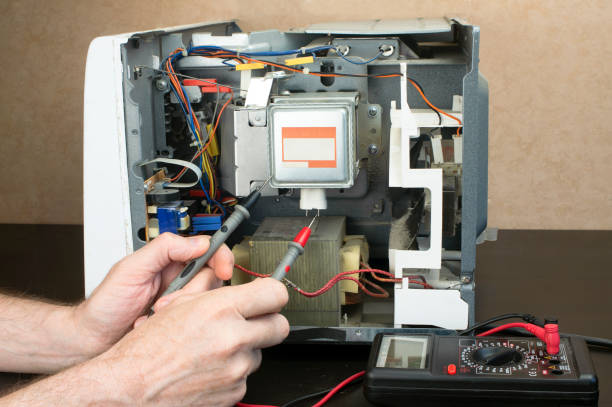 Repair of a microwave oven, repair of household appliances. The master measures the voltage with a tester stock photo