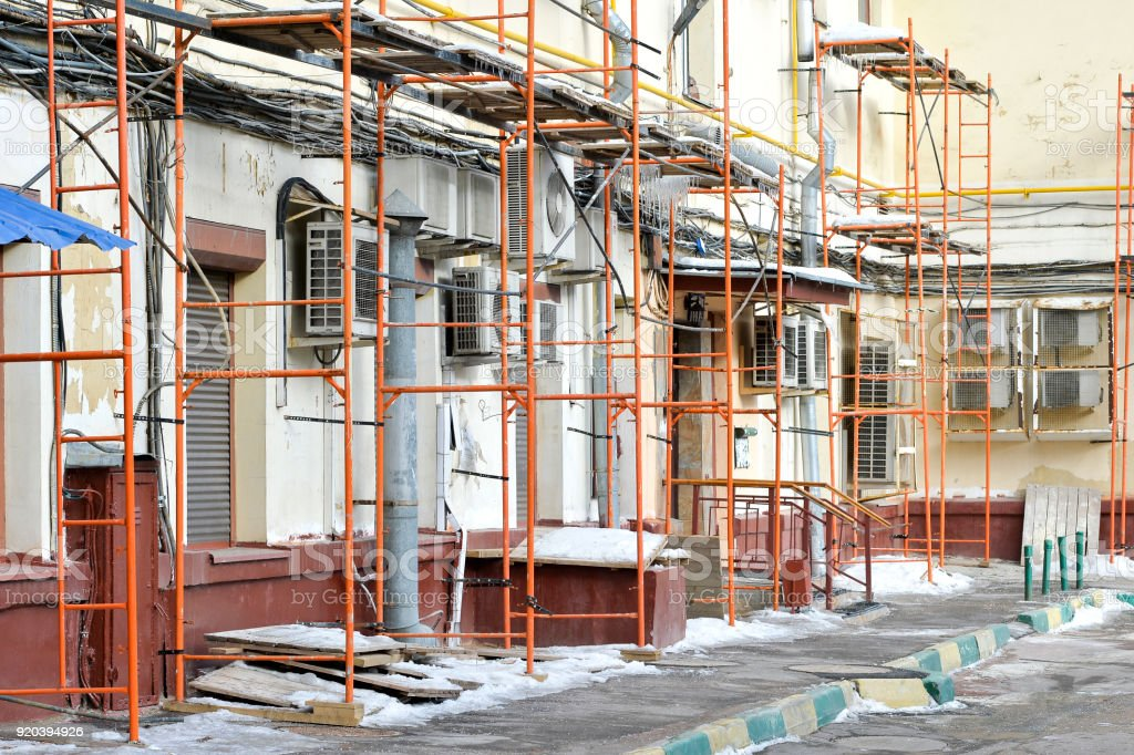 Repair of a residential building scaffolding on the background of numerous communications in the home in the winter. No body. stock photo