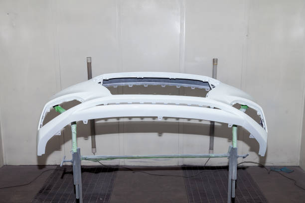 Repair of the rear bumper of a white car after an accident with the help of multi-colored putty in a workshop for painting vehicles in a special chamber stock photo