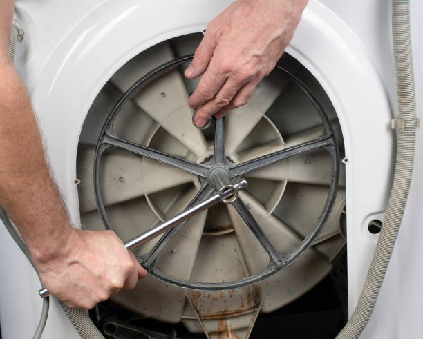 Repair of washing machines, repair of large household appliances. Plumber removes parts from a washing machine stock photo