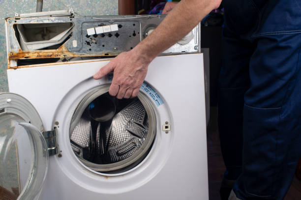 Repair of washing machines, repair of large household appliances. Repairman disassembles a washing machine for parts stock photo