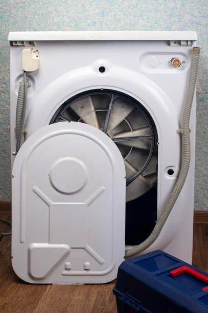 Repair of washing machines, repair of large household appliances. The back of the washing machine is removed, there is a tool box stock photo