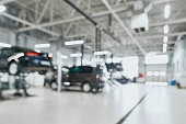 Repair service station with lifted modern cars being under maintenance and technicians on blurred background with many diode lamps. Auto service and technician concept
