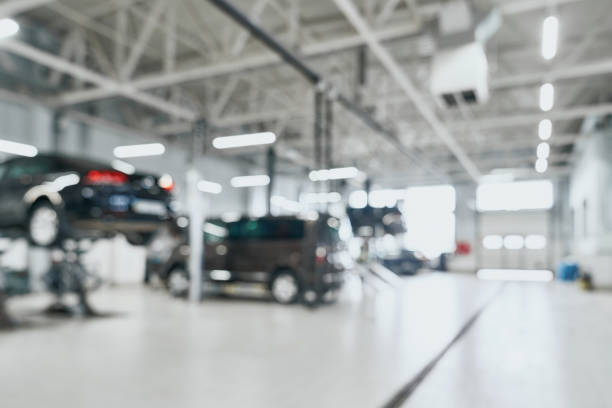 reparaturstation mit angehobenen modernen autos, die unter wartung stehen, und techniker auf verschwommenem hintergrund mit vielen diodenlampen. auto-service und techniker-konzept - autowerkstatt stock-fotos und bilder